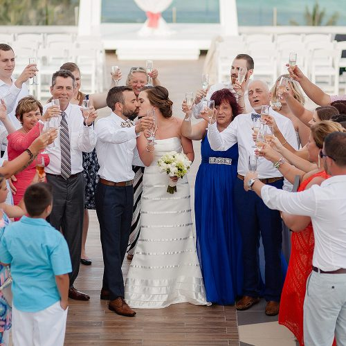Bride and groom kissing with guests all around