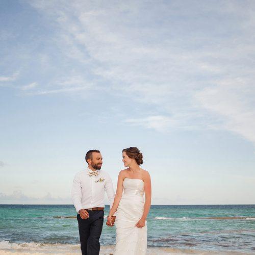 Bride and groom walking on beach at Azul Fives Hotel, Riviera Maya