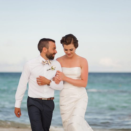 Close up of bride and groom walking on beach.