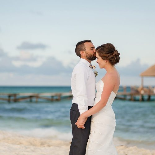 Groom kissing bride on beach at Azul Fives Hotel, Riviera Maya