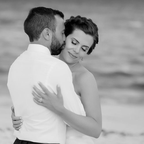 Bride and groom on beach after wedding.