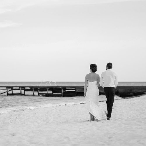 Black and white of bride + groom walking on beach at Azul Fives Hotel, Riviera Maya
