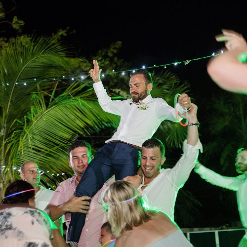 Groom being carried on shoulders of guests dancing at wedding reception