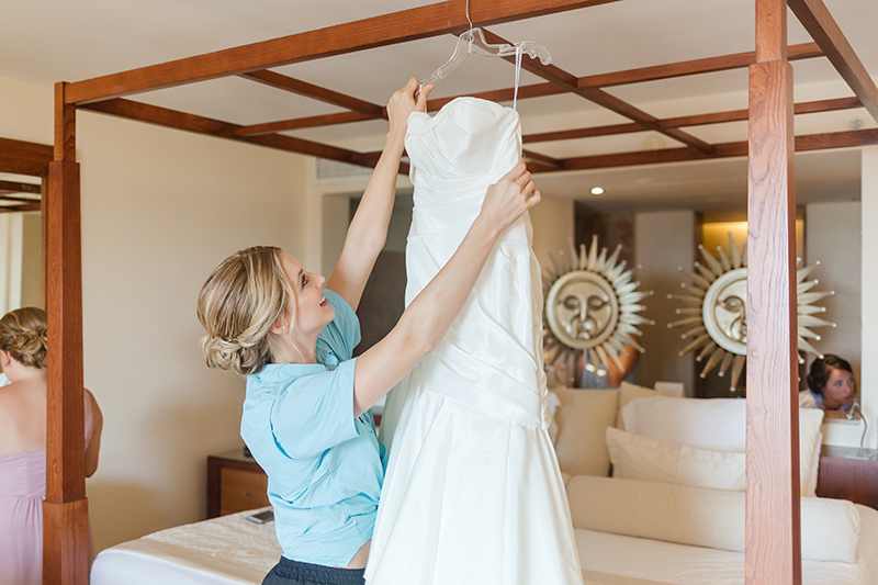 Bride getting dress down at Excellence Playa Mujeres wedding