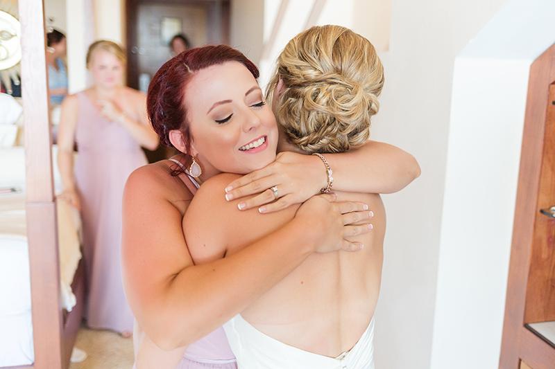 Bridesmaid hugging bride at Excellence Playa Mujeres