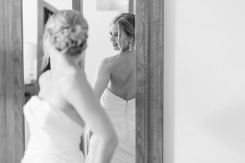 Bride looking at herself in mirror before wedding