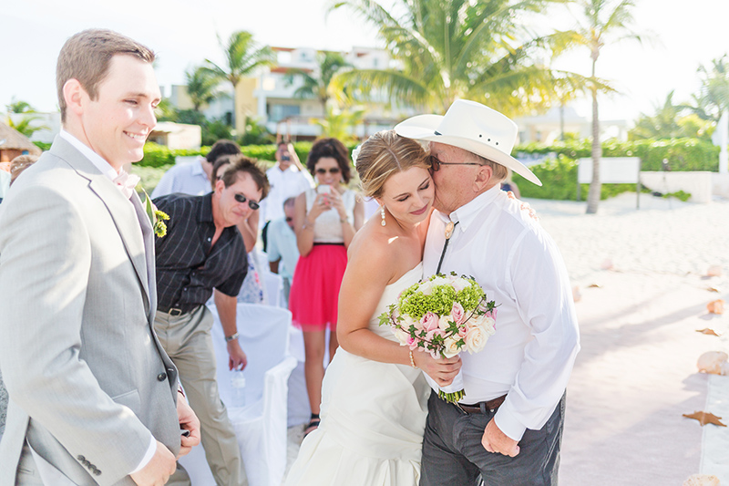 Bride hugging father after walking down aisle.
