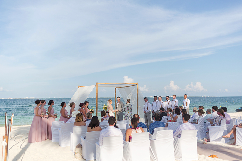 Bride and groom at wedding ceremony on beach at Excellence Playa Mujeres