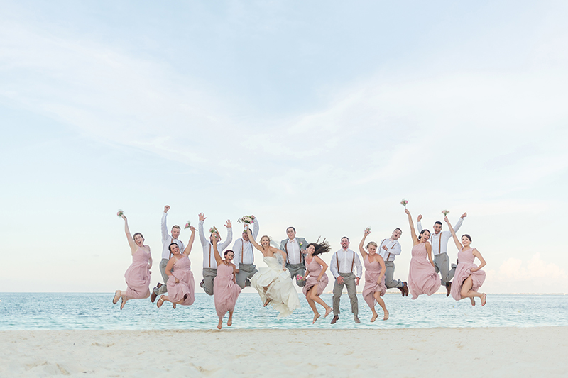 Bridal party jumping on beach after wedding in Cancun