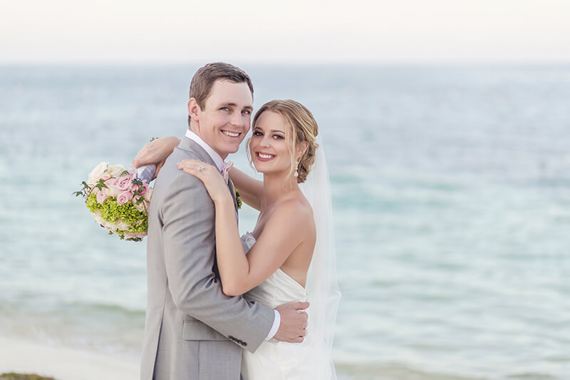 Bride and groom laughing on Excellence Playa Mujeres beach wedding