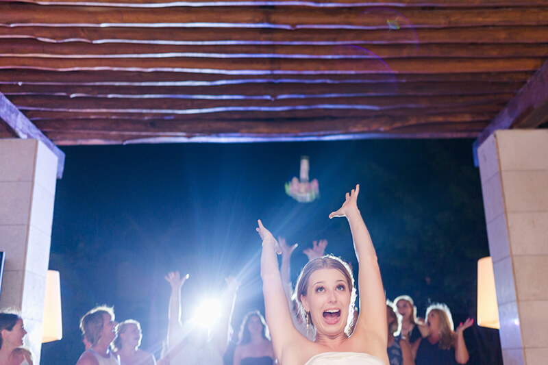 Bride tossing bouquet at wedding