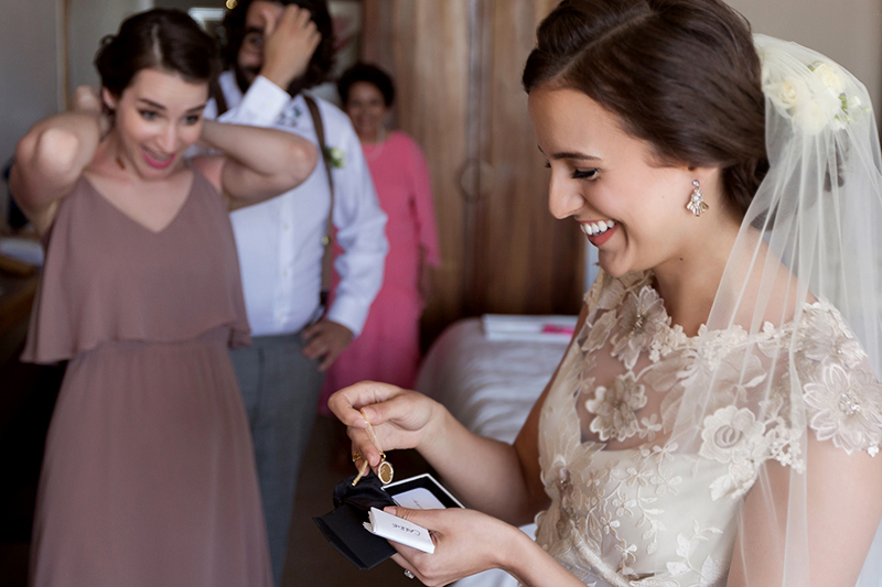 Bride opening gift from groom in Tulum