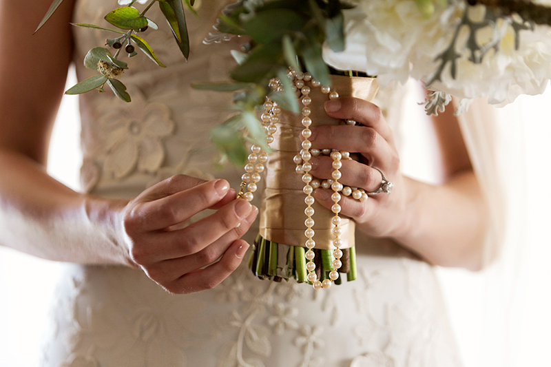 Close up of pearls under bridal bouquet