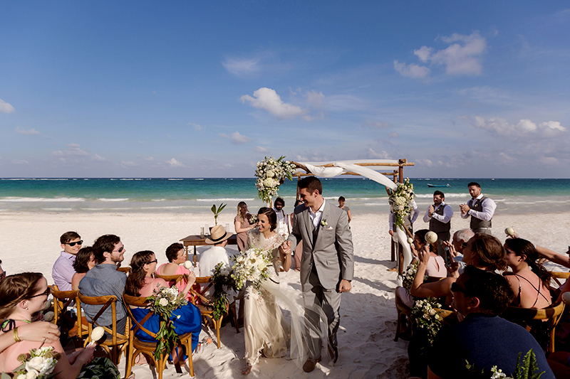 Bride and groom celebrate after wedding on beach in Tulum