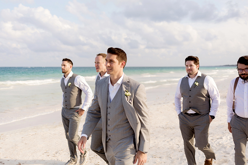 Groom walking down beach with groomsmen