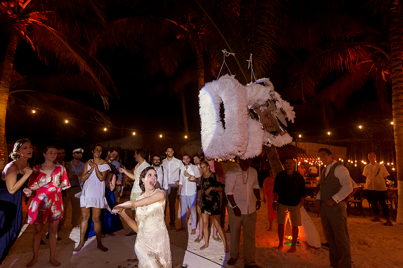 Bride hitting Piñata at Tulum wedding