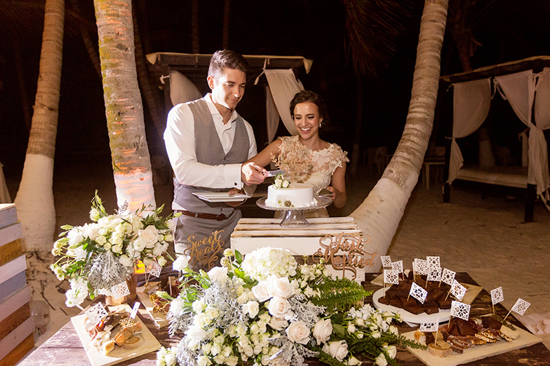 Bride and groom cutting cake at wedding in Tulum