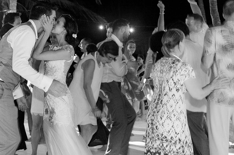 Bride and groom kissing on dance floor in Tulum