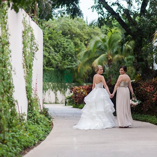 Bride and bridesmaid before wedding on walkway at Azul Fives Hotel, Riviera Maya