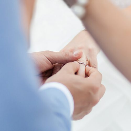 Close up of groom putting on ring