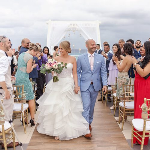 Bride and groom walking down aisle after wedding on sky deck at Azul Fives Hotel