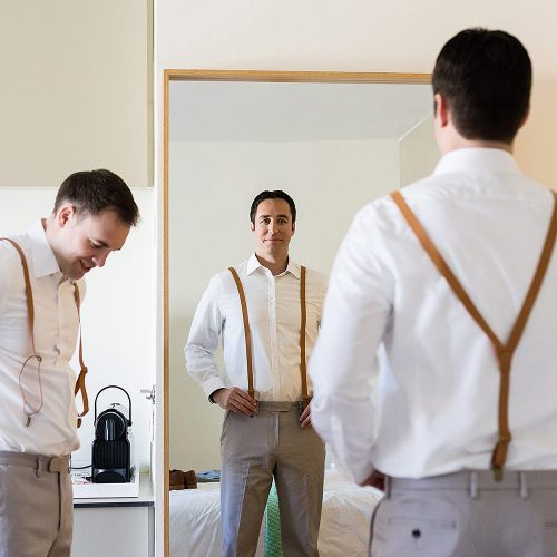 Groomsman looking in mirror getting ready at Finest Playa Mujeres Resort