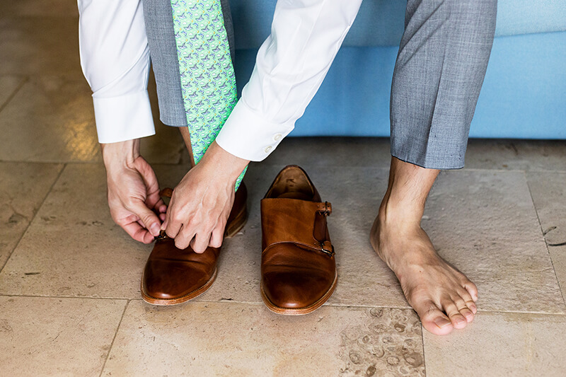 Close up of groom putting on shoes before wedding