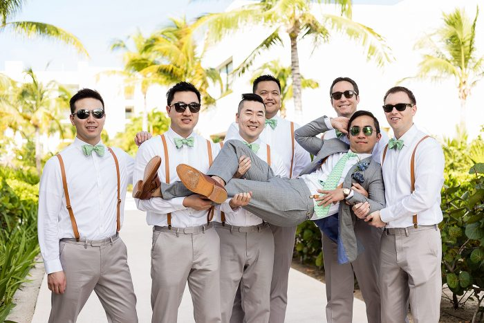 Groomsmen holding groom before wedding in Cancun