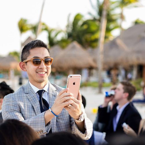 Guest taking photo with phone at wedding ceremony in Cancun