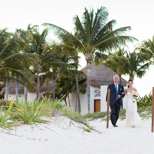 Bride walking with father to wedding reception on beach in Cancun