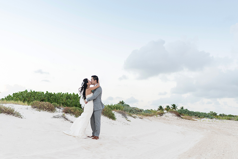 Bride and Groom on beach kissing at Finest Playa Mujeres Resort