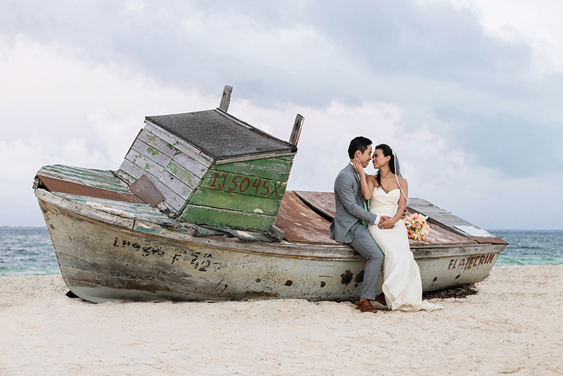 Bride and groom on beach beside shipwreck on beach near Finest Playa Mujeres Resort