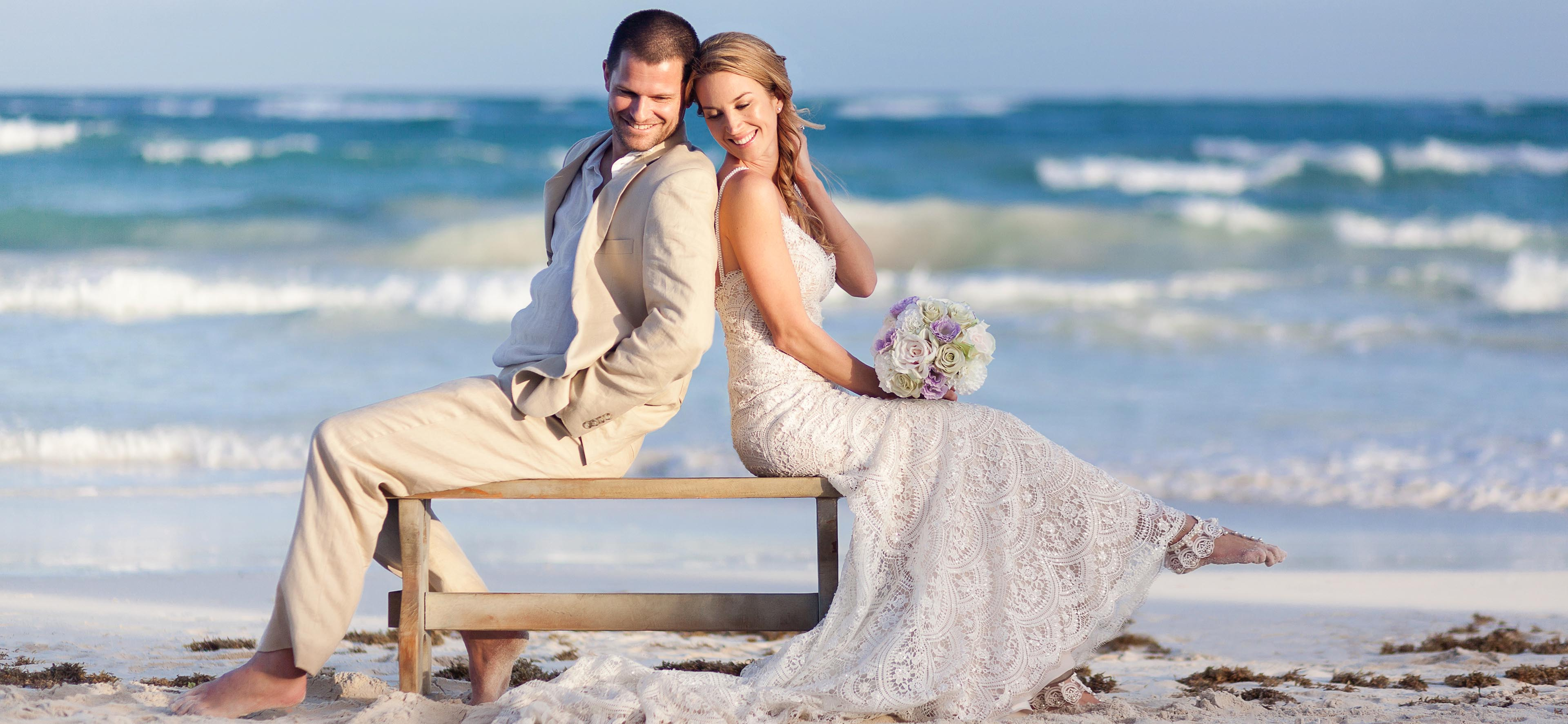 Bride and Groom sitting on Bench on beach in Tulum.