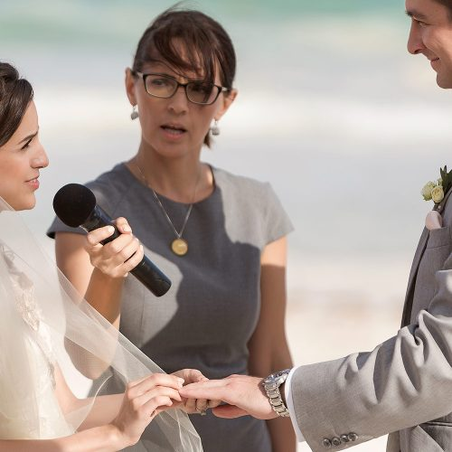 Bride giving groom ring at wedding in Tulum