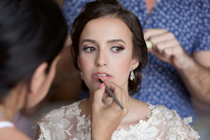 Bride getting final touches of makeup at wedding in Tulum.