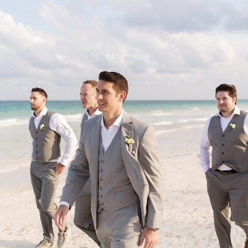 Groomsmen walking on beach in Tulum