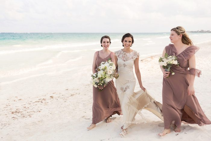 Bridesmaids walking on beach in Tulum wedding