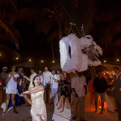 Bride hitting piñata at wedding in Tulum