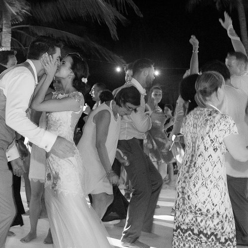 Bride and groom kissing on dance floor at Tulum wedding
