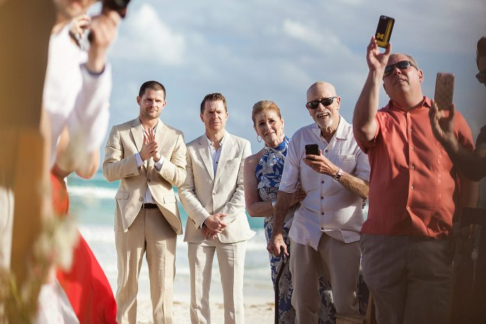 Guests taking photographs with phones as bride walks down the aisle in Tulum wedding