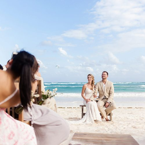 Bride and groom on bench at wedding ceremony at Akiin Tulum