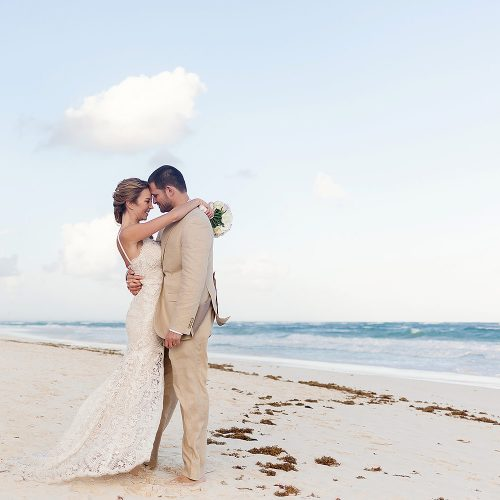 Bride and groom kissing on beach in Tulum.