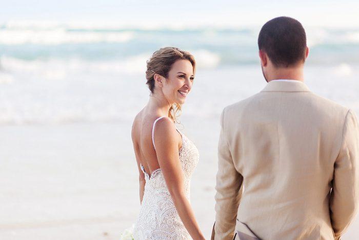 Bride looking at groom on beach in Tulum