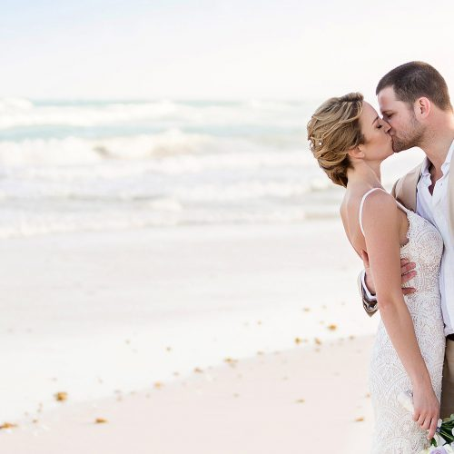 Groom kissing bride on beach in Tulum after wedding