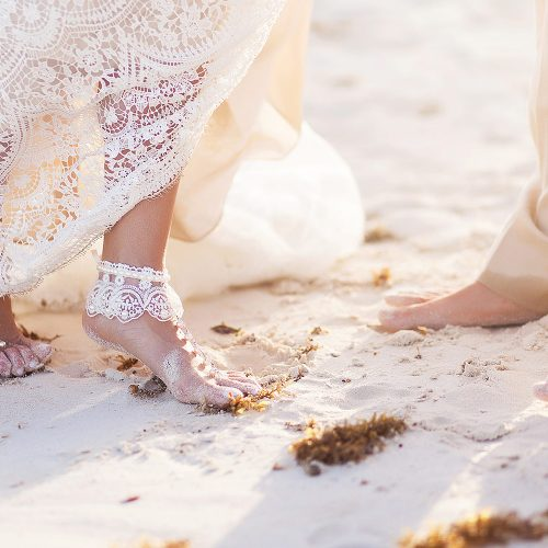 Close up of brides feet on beach in Tulum