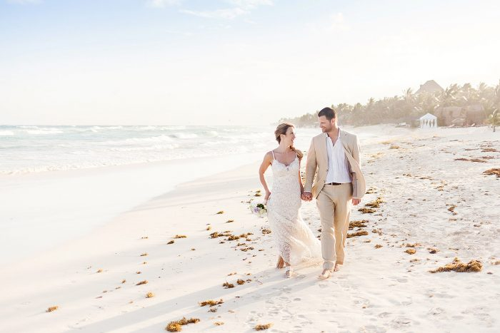 Bride and groom walking down beach in Tulum