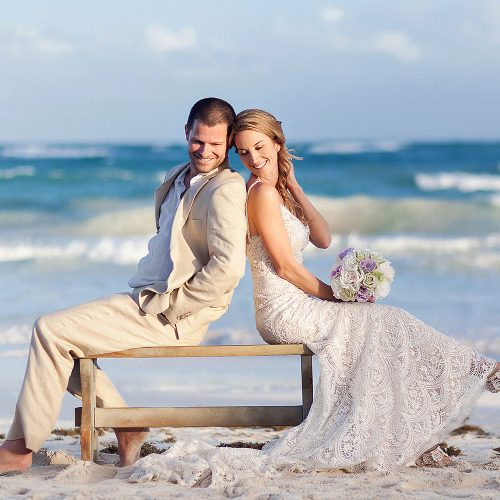Bride and groom on bench in Tulum