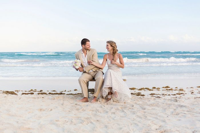 Bride and groom having fun on bench an beach in Tulum