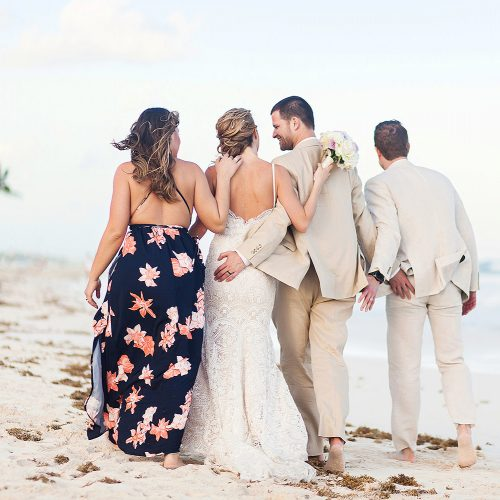 Bridal party walking on beach in Tulum