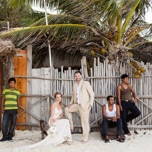 Portait of bride with locals on beach in Tulum